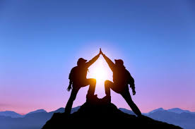Rockclimbers on top of mountain touching hands